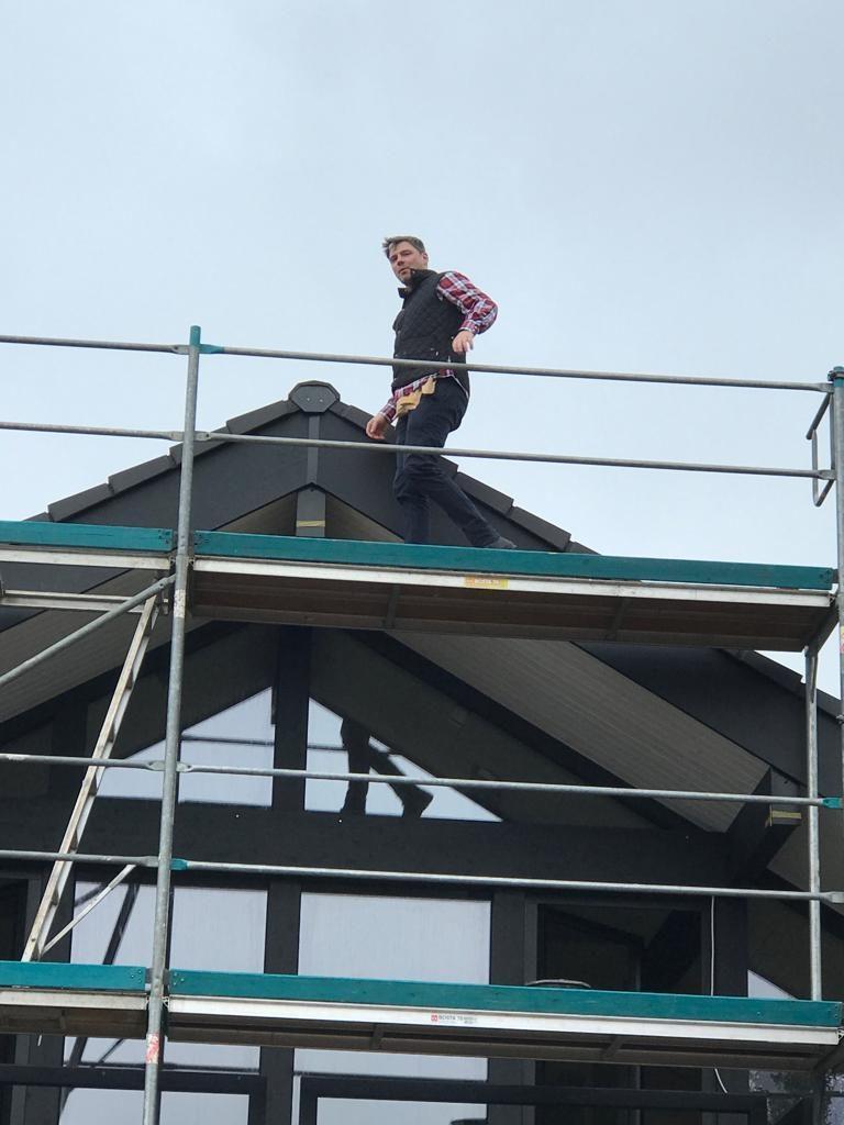 Tobis Beuler auf Dach, davor Gerüst