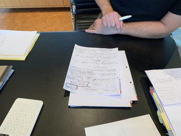 Mann sitzt mit Unterlagen am Schreibtisch