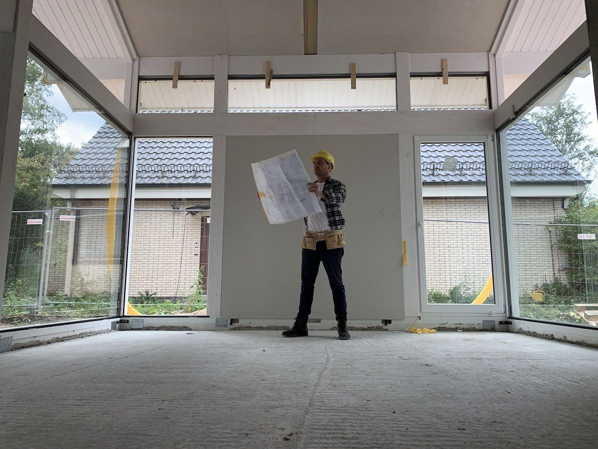 Ein Mann mit Bauplan steht in einem Haus