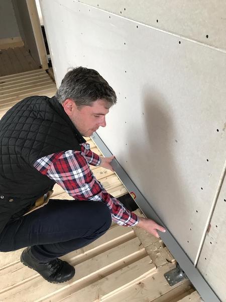 Mann misst eine Wand ab