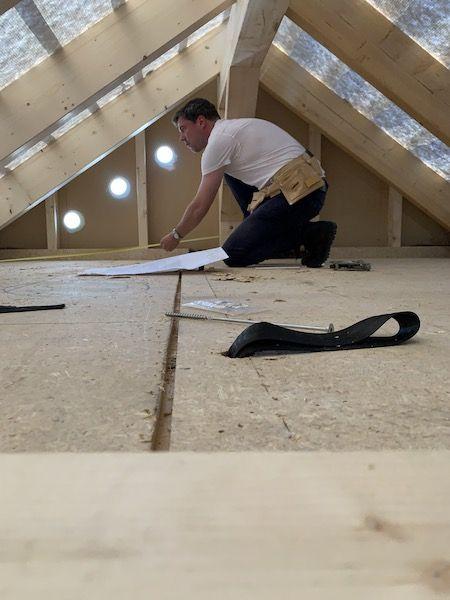 Mann ist auf einem Dachboden mit Bauplan
