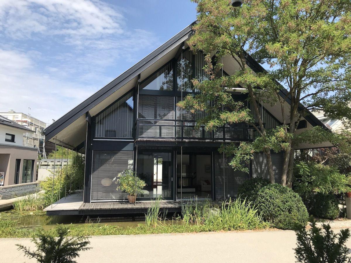 Ein modernes Haus von außen, das leicht von einem Baum verdeckt wird