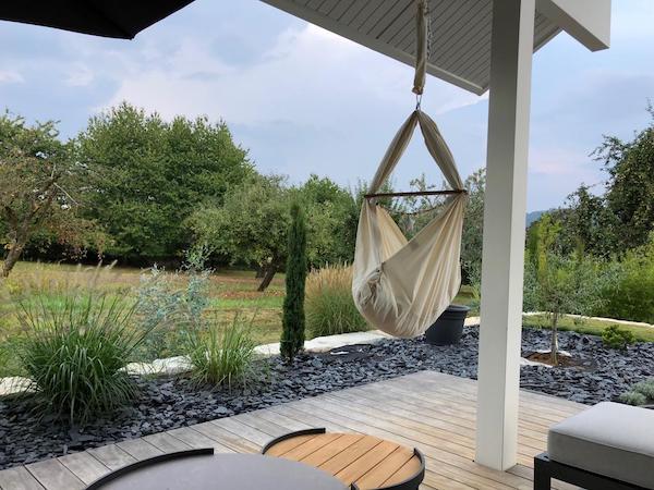 Eine Terrasse mit Hängematte in einem großen Garten