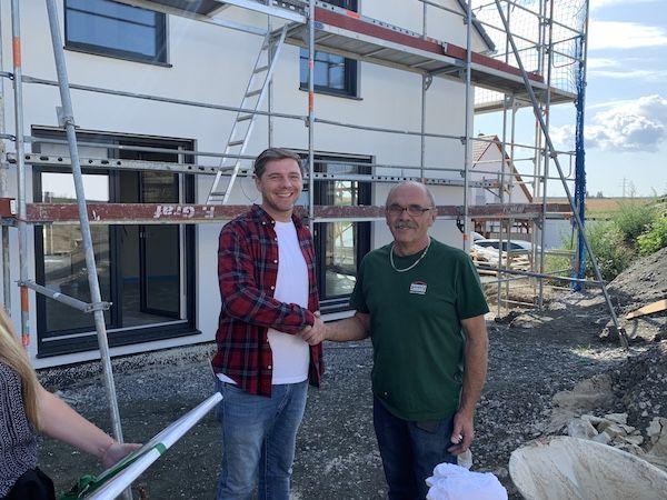 Zwei Männer schütteln sich die Hand vor einem Neubau