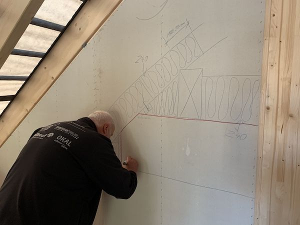 Mann zeichnet Plan an die Wand