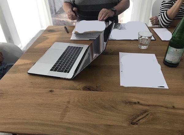 Laptop am Tisch mit Unterlagen zum Hausbau