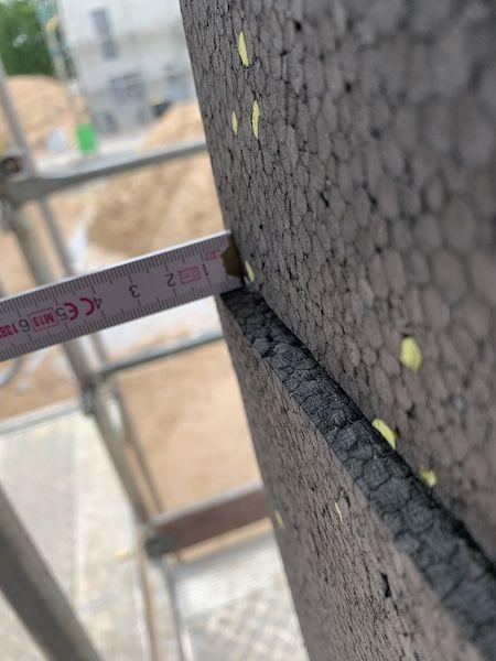 Ein Zollstock mit dem die Wand gemessen wird
