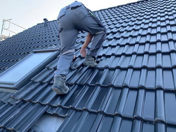 Ein Dachdecker geht auf ein Gussek Haus Dach