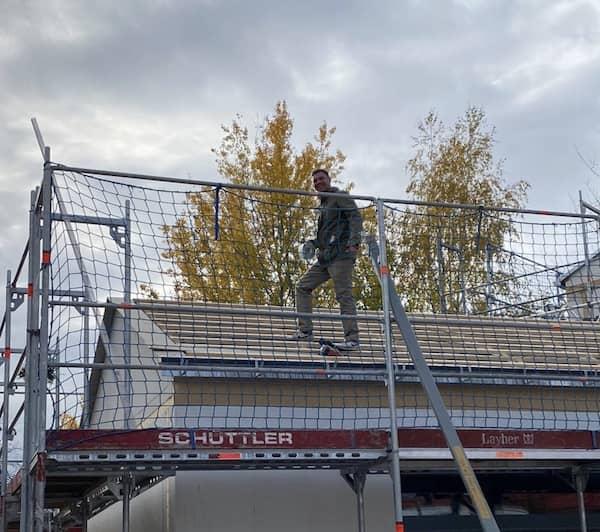 Der Fertighausexperte Tobias Beuler auf einem Hausdach